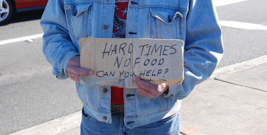 A man in Kirkland, Washington holds handwritten sign asking for help.